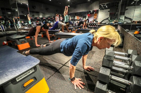 Courier Journal reporter Kirby Adams works out during a morning session at Shred 4/15. The workout consists of cardio on treadmills and core/strength training.