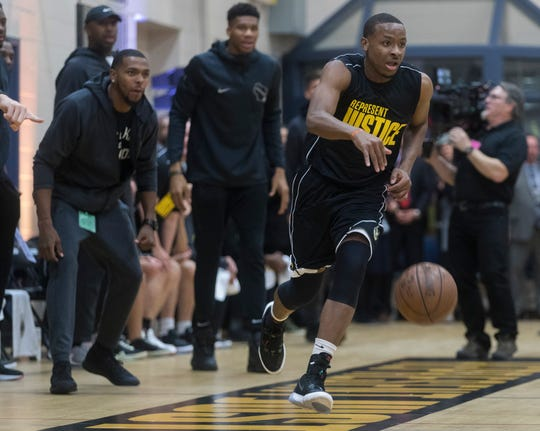 Equan Taylor sprints past his bench and his coach, Milwaukee Bucks forward Giannis Antetokounmpo, during a game  at the Racine Correctional Institution in Sturtevant on Tuesday.