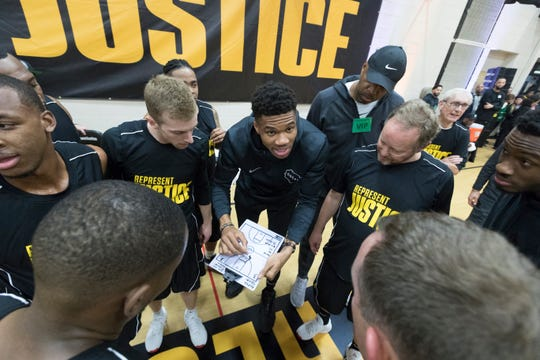 """Milwaukee Bucks forward Giannis Antetokounmpo, center, instructs his team of Bucks staff, notables and incarcerated people at the Racine Correctional Institution in Sturtevant on Tuesday. The Bucks were there as part of the NBA's """"Play for Justice"""" initiative and the Anti-Recidivism Coalition, a group whose mission is to support incarcerated and formerly incarcerated people. Before the game, there was a roundtable discussion among participants about topics such as criminal justice reform. Gov. Tony Evers, rear right, also participated."""