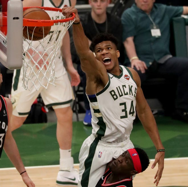Milwaukee Bucks forward Giannis Antetokounmpo dunks over the Toronto Raptors' Pascal Siakam and Marc Gasol during the first quarter of Game 2 of the Eastern Conference finals NBA playoffs at Fiserv Forum on May 17.