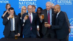Democratic National Committee Chairman Tom Perez, center, reacts after spilling a celebratory beer on the convention contract with, from left,  Milwaukee Bucks Senior Vice President Alex Lasry, Milwaukee Mayor Tom Barrett and Lt.  Gov. Mandela Barnes on March 11, 2019, following the official announcement that Milwaukee will host the 2020 Democratic National Convention at Fiserv Forum.