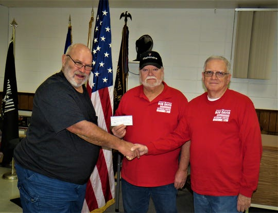 North Arkansas Woodcarvers Club president Marty Wells (left) presents Roger Smith and James Johnson with a $600 donation to the Bob Davis Veterans Shelter.