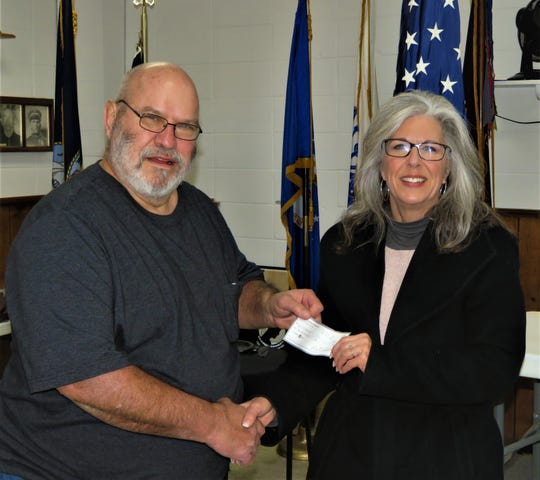 North Arkansas Woodcarvers Club president Marty Wells presents a $600 donation to Serenity Inc. executive director Donna Forrester.