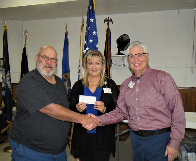 North Arkansas Woodcarvers Club president Marty Wells (left) presents a $600 donation for Hospice of the Ozarks to Elaine Essary and Craig Wood.
