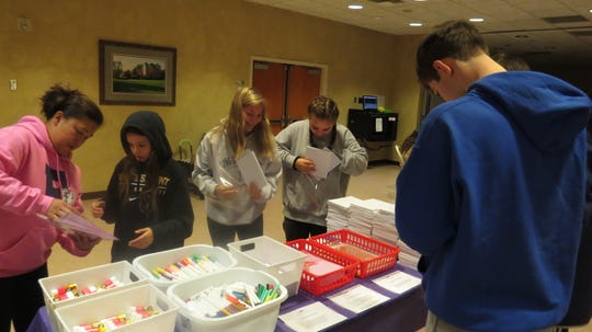Volunteer students at St. Matthew the Apostle Church in Randolph assemble special journal kits that immigrant children on the U.S. border can document their thoughts and hopes as they try to make a new life in a new country.  Dec. 8, 2019.