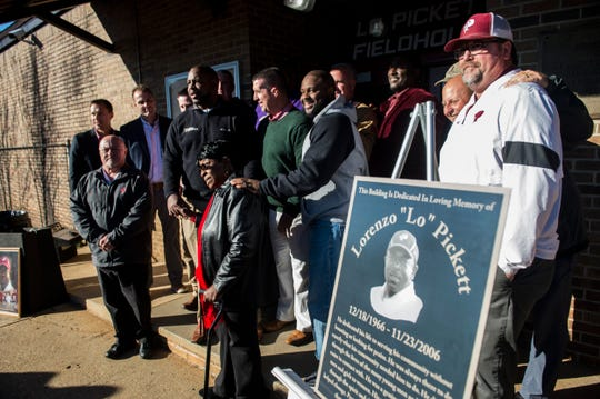 """Louise Pickett Jones, mother, poses with fellow coaches during a dedication of the Lo Pickett Fieldhouse at Prattville High School in Prattville, Ala., on Wednesday, Dec. 18, 2019. Lorenzo """"Lo"""" Pickett was a coach at Prattville High until he died of a heart attack in 2006 at the age of 40."""