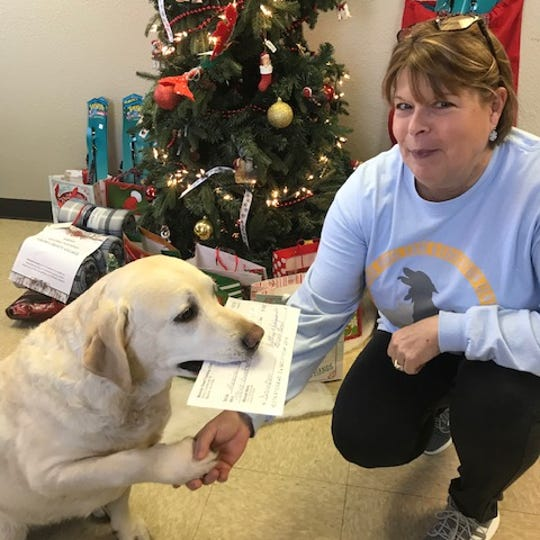 Darby Dalessandro (left), representing the Muncie Obedience Training Club, presents a check for $310 to Molly Morrison of Muncie Animal Care and Services.