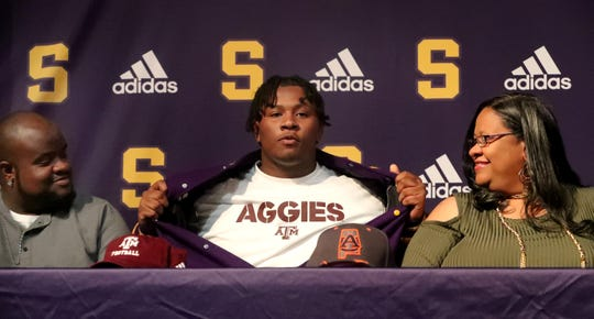Smyrna Football player Dallas Walker, center opens his jacket to announce that he will be signing to play football with Texas A&M, during early signing day, on Wednesday Dec. 18, 2019 at Smyrna. Walker's brother Aaron Short, left, and mother Sandra Whitaker, right, watch is announcement.