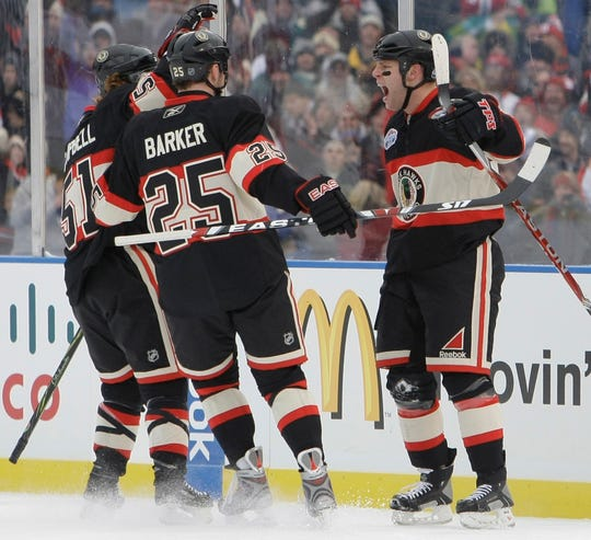 Chicago Blackhawks' Ben Eager, right, celebrates his goal with teammates Brian Campbell and Cameron Barker during the first period of the NHL Winter Classic hockey game against the Detroit Red Wings at Wrigley Field, Thursday Jan. 1, 2009, in Chicago. (AP Photo/Nam Y. Huh)