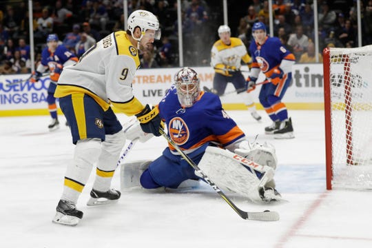 New York Islanders goaltender Semyon Varlamov, right, defends against Nashville Predators' Filip Forsberg during the third period of an NHL hockey game Tuesday, Dec. 17, 2019, in Uniondale, N.Y. The Predators won 8-3.