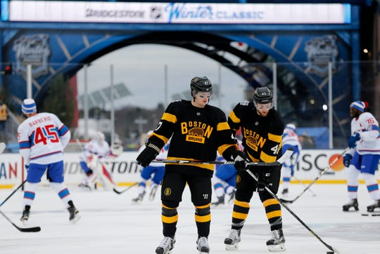 Boston Bruins' Torey Krug (47) and Joe Morrow (45) warm up before the NHL Winter Classic hockey game against the Montreal Canadiens at Gillette Stadium in Foxborough, Mass., Friday, Jan. 1, 2016. The Canadiens won 5-1. (AP Photo/Michael Dwyer)