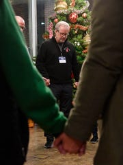 Jim Brown, a volunteer at Room in the Inn, prays with other volunteers before they all help about 200 homeless break into groups to travel to different congregations for the night Sunday Dec. 8, 2019, in Nashville, Tenn.