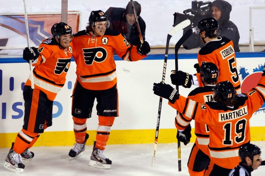 Philadelphia Flyers' Kimmo Timonen, from left, of Finland, Claude Giroux, Braydon Coburn, Maxime Talbot and Scott Hartnell celebrate after Giroux's goal in the second period of the NHL Winter Classic hockey game against the New York Rangers, Monday, Jan. 2, 2012, in Philadelphia. (AP Photo/Mel Evans)