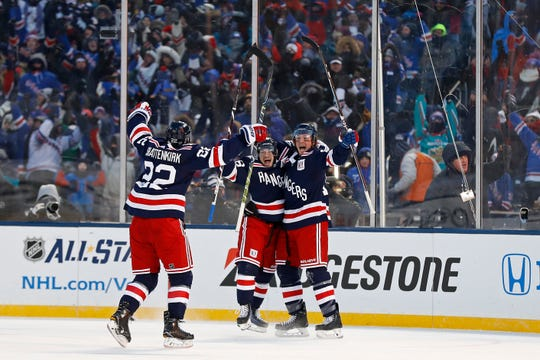 New York Rangers left wing J.T. Miller (10) celebrates scoring the game winning goal with Rangers right wing Mats Zuccarello (36) and Rangers defenseman Kevin Shattenkirk (22) against the Buffalo Sabres in overtime of the NHL Winter Classic hockey game at CitiField in New York on Monday, Jan. 1, 2018. The Rangers won 3-2. (AP Photo/Adam Hunger)