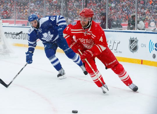 Detroit Red Wings defenseman Jakub Kindl (4), of the Czech Republic, controls the puck in front of Toronto Maple Leafs left wing Nikolai Kulemin (41), of Russia, during the first period of the Winter Classic outdoor NHL hockey game at Michigan Stadium in Ann Arbor, Mich., Wednesday, Jan. 1, 2014. (AP Photo/Paul Sancya)