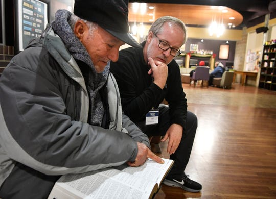 """Jim Brown, a volunteer at Room in the Inn, talks with Victor Gonzalez, 70, from Cuba, who pulled a new Bible out of his bag to show Brown, who took it gently: """"This is beautiful,"""" Brown said softly as Gonzalez smiled Sunday Dec. 8, 2019, in Nashville, Tenn."""