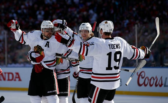 Chicago Blackhawks left wing Patrick Sharp, left, celebrates his goal with center Jonathan Toews (19) and others in the first period of the Winter Classic outdoor NHL hockey game against the Washington Capitals at Nationals Park, Thursday, Jan. 1, 2015, in Washington. (AP Photo/Alex Brandon)