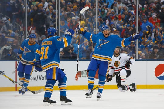 St. Louis Blues' Vladimir Tarasenko, second from left, of Russia, celebrates with Jori Lehtera, third from left, and Robby Fabbri, left, as Chicago Blackhawks' Brent Seabrook, right, of Finland, looks on after Tarasenko scored a goal during the third period of the NHL Winter Classic hockey game at Busch Stadium, Monday, Jan. 2, 2017, in St. Louis. (AP Photo/Billy Hurst)
