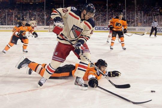 Philadelphia Flyers' Braydon Coburn, bottom, battles for the puck with New York Rangers' Marian Gaborik, of Slovakia, in the second period of the NHL Winter Classic hockey game, Monday, Jan. 2, 2012, in Philadelphia. (AP Photo/Matt Slocum)