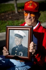 Lou Rauschenberger holds a photo of himself from when he was in the Marine Corps as he poses for a portrait at American House in Bonita Springs on Monday, December 16, 2019.