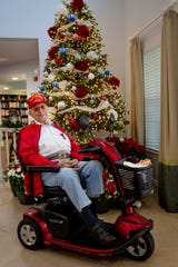 Lou Rauschenberger poses for a portrait in front of the Christmas tree at American House in Bonita Springs on Monday, December 16, 2019.