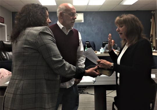 Sandra Salviano is sworn in by North Haledon Mayor Randy George to fill a seat previously held by her late husband on the Borough Council, as council president Donna Puglisi holds the Bible on Dec. 17.