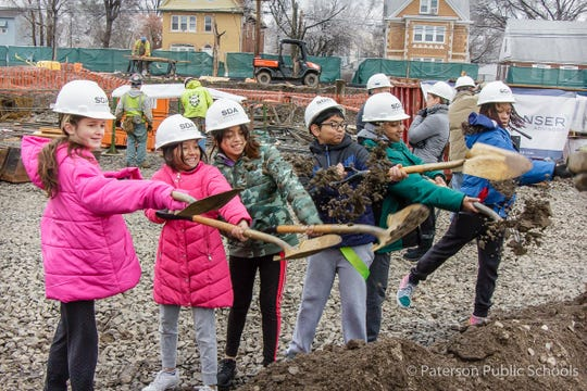 Students who will be in the 7th grade when the new  Union Avenue School opens in September 2021 move the first shovelfuls of dirt at the school's construction site on Wednesday, Dec. 18.