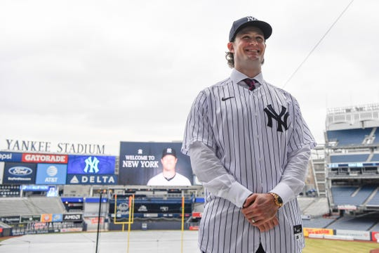 New York Yankees pitcher Gerrit Cole poses in front of the field at Yankee Stadium.