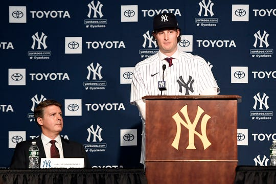 Pitcher Gerrit Cole speaks during a press conference as New York Yankees owner Hal Steinbrenner, left, looks on at Yankee Stadium on Wednesday, Dec. 18, 2019, in New York.