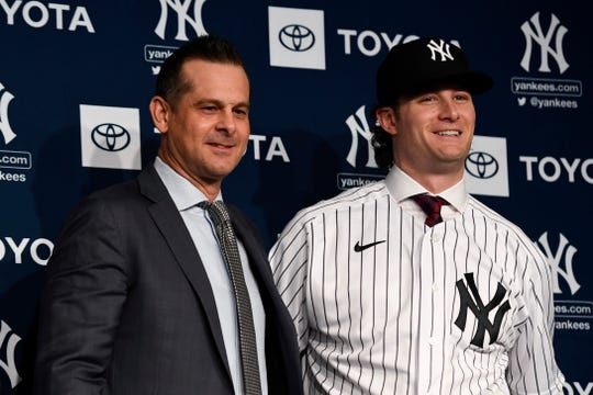 New York Yankees manager Aaron Boone, left, and pitcher Gerrit Cole pose for photos during a press conference at Legends Club at Yankee Stadium.