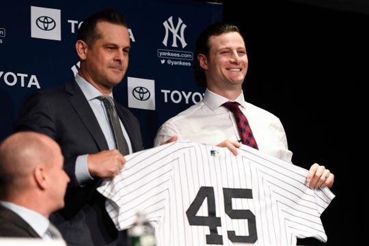 Yankees manager Aaron Boone, left, poses with new Yankee pitcher Gerrit Cole during a press conference at Legends Club at Yankee Stadium.