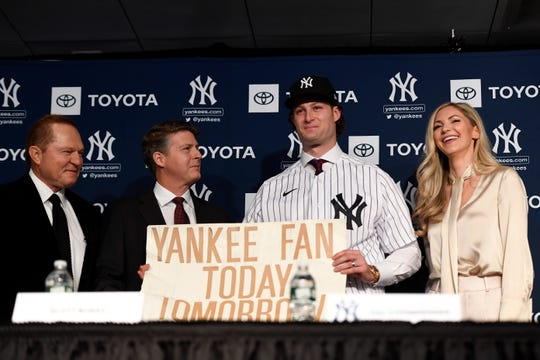 Pitcher Gerrit Cole, second from right, holds the sign he was photographed holding at the 2001 World Series as a kid as he poses for photos with, from left, Scott Boras, Hal Steinbrenner, and his wife Amy during a press conference at Legends Club at Yankee Stadium.