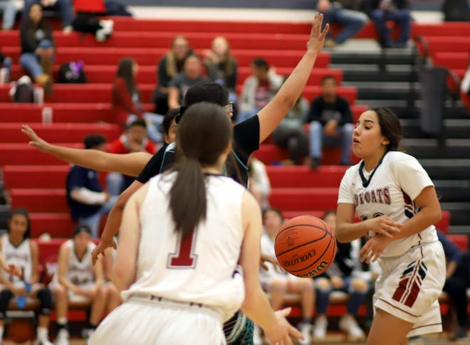Senior Lady 'Cat guard Nicole Lopez (at right) shared the basketball in Deming's 57-24 victory over Santa Teresa High Tuesday at Deming High School.