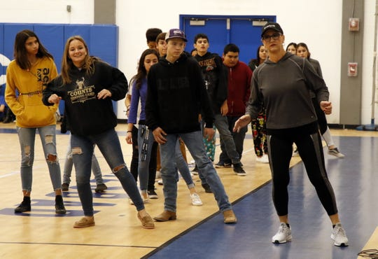 Left to right: Carlsbad High students Monica Watts, Myles Klein and PE teacher Bonnie McKenzie go over the dance steps for the electric slide during class on Dec. 18, 2019. The final two weeks of PE classes in December focus on dancing to give the students a chance for indoor exercise during the Christmas break.