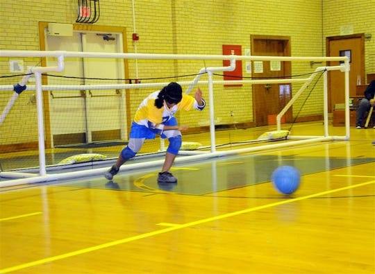 Mary Nix rolls the ball toward the opposing team during the New Mexico School for the Blind and Visually Impaired goalball match against Colorado School for the Deaf and Blind Dec. 13.