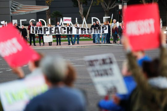 Protesters hold signs during an impeachment rally in Phoenix on Dec. 17, 2019. The nationwide rally comes on the eve of the House of Representatives vote on impeaching President Trump.