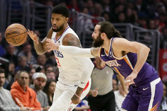 Los Angeles Clippers forward Paul George, left, and Phoenix Suns guard Ricky Rubio chase a loose ball during the first half of an NBA basketball game in Los Angeles, Tuesday, Dec. 17, 2019. (AP Photo/Chris Carlson)