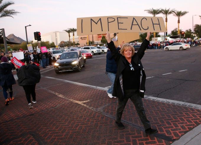 A protester carries a sign while crossing Camelback Road during an impeachment rally in Phoenix on Dec. 17, 2019. The nationwide rally comes on the eve of the House of Representatives vote on impeaching President Trump.