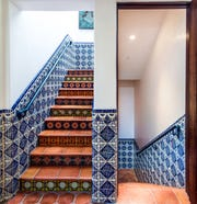 Staircases that lead to the second floor and basement are enveloped in custom hand-painted tiles in colors that were mixed on site by the artist. Power outlet covers were hand-painted to seamlessly meld into the pattern, rendering them nearly undetectable.