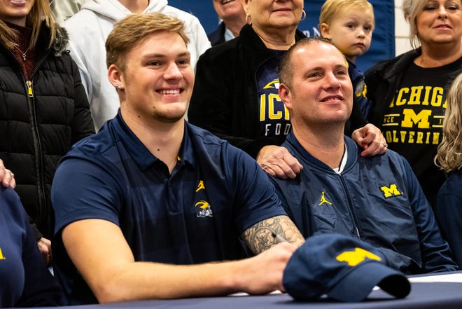 Port Huron Northern senior Braiden McGregor, left, with his family after signing his letter of intent to Michigan Wednesday, Dec. 18, 2019, in the gymnasium at Port Huron Northern. McGregor, a four-star recruit, announced he was committing to play football at Michigan in May.