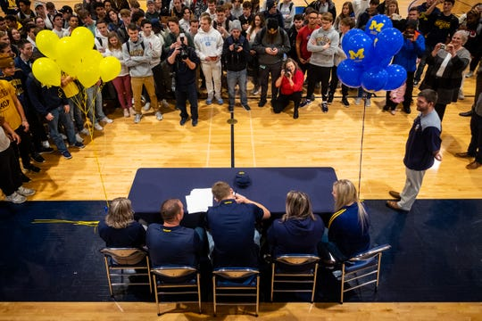 Port Huron Northern senior Braiden McGregor, center, is surrounded by his coaches, family, friends and students as he signs his letter of intent to Michigan Wednesday, Dec. 18, 2019, in the gymnasium at Port Huron Northern. McGregor, a four-star recruit, announced he was committing to play football at Michigan in May.