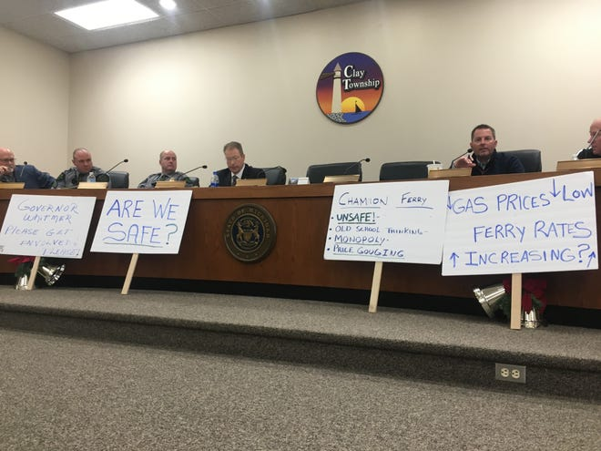 Signs brought by attendees express concerns about Champion's Auto Ferry at a meeting about high water levels and ferry rates in Clay Township on Dec. 18, 2019.