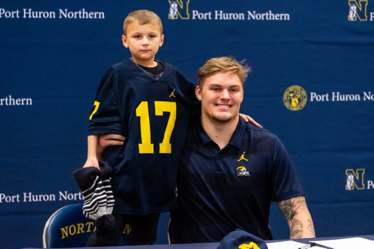 Port Huron Northern senior Braiden McGregor poses for a photo with Carter Lumley, 8, who is wearing McGregor's jersey Wednesday, Dec. 18, 2019, in the gym at Port Huron Northern.