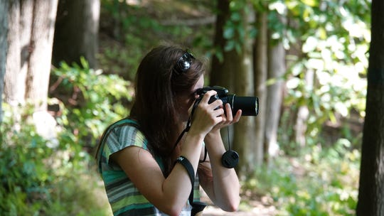 "Emily Stoll, a member of the New York State Young Birders Club, is shown birding at Teatown Lake Reservation. ""I am looking at a bird and trying to hold still so that I can take a good picture,"" she said."