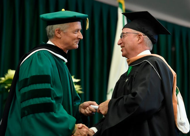 Jeff Hines, president of York Water Company and York College Chair of Trustees, left, awards JT Hand, CCO of York Water Company, his diploma during the York College Winter Commencement, Wednesday, December 18, 2019. Hand, along with five other Water Company and Shipley Energy employees, earned their Masters of Business Administration in a two-year accelerated program. John A. Pavoncello photo