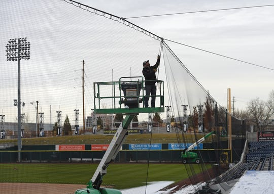 Billy Norghey with J. Hicks Sports Installation works on installing the new retractable protective netting at Aces ballpark to protect baseball fans from getting hit by a foul ball during Aces games.