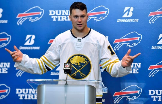 Buffalo Bills quarterback Josh Allen shows off the colors of his favorite NHL team, the Buffalo Sabres. Allen received a congratulatory text message from Sabres star Jack Eichel after the Bills beat the Steelers to clinch playoff spot.
