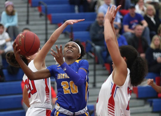 Irondequoit's Alahna Paige drives through Fairport's Bella Pucci (20) and Ella Meabon on Dec. 17. Paige scored 33 points to become Irondequoit's career scoring leader with 1,310.