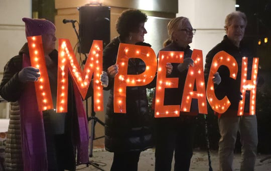 Supporters of impeaching President Trump hold lighted letters that spell impeach outside Redding City Hall on Tuesday, Dec. 17, 2019.