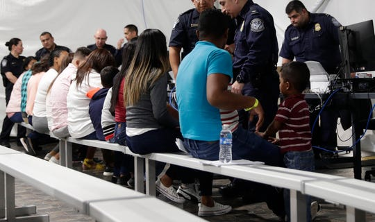 """In this Sept. 17, 2019, file photo, migrants who are applying for asylum in the United States go through a processing area at a new tent courtroom at the Migration Protection Protocols Immigration Hearing Facility in Laredo, Texas. Law groups representing immigrants say the immigration court system under the Trump administration has become a """"deportation machine."""" A lawsuit filed in federal court in Portland, Oregon, on Wednesday, Dec. 18, 2019 says that instead of being impartial in decisions that often are life-and-death matters, the immigration courts have the ultimate goal of deportation."""